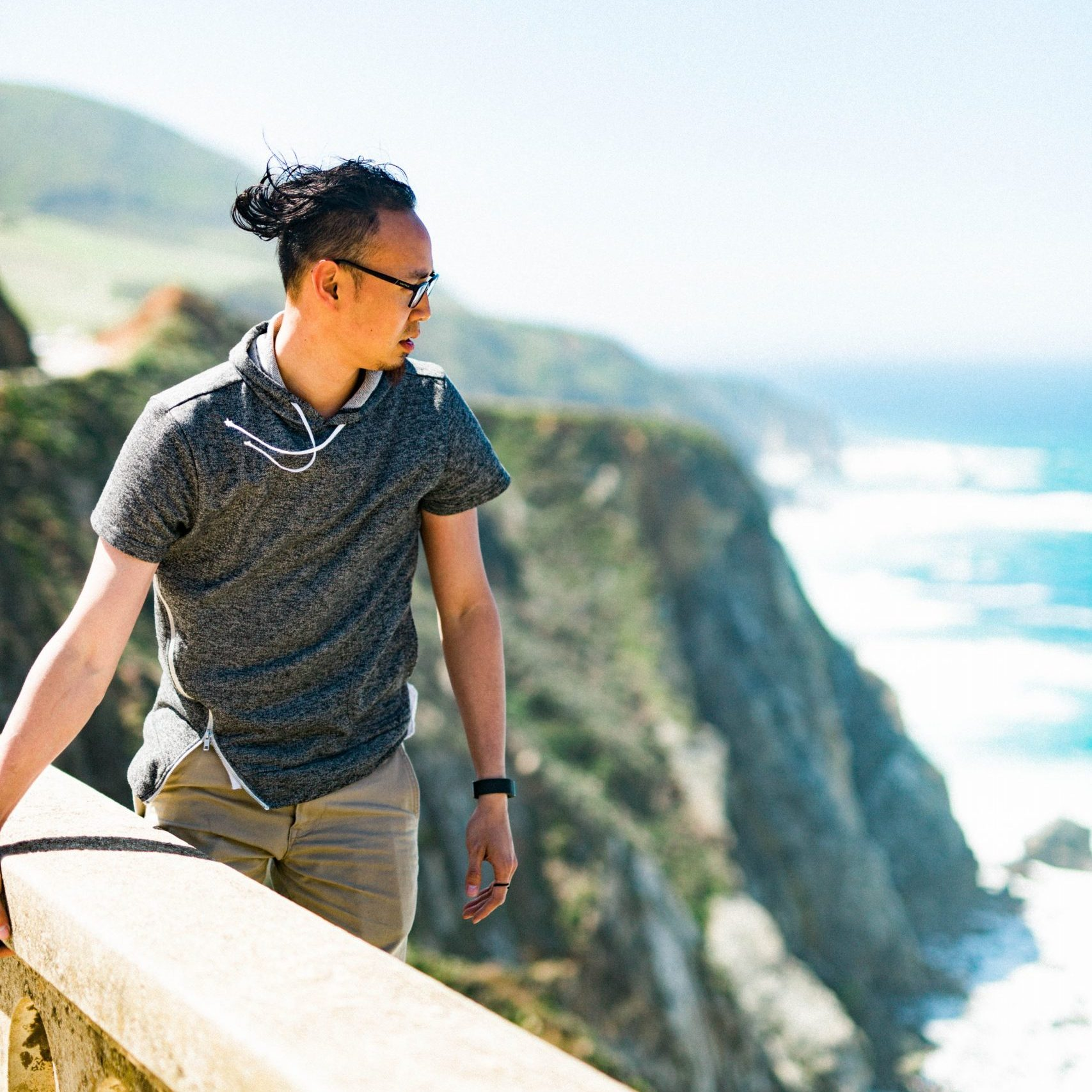 man standing on cliff while holding concrete barrier